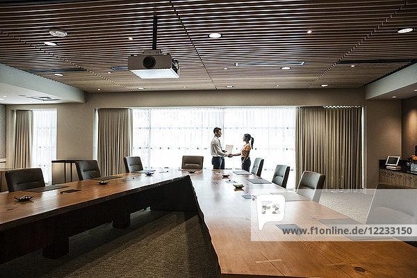 Geschäftsfrau und Mann treffen sich in einem großen Konferenzraum.