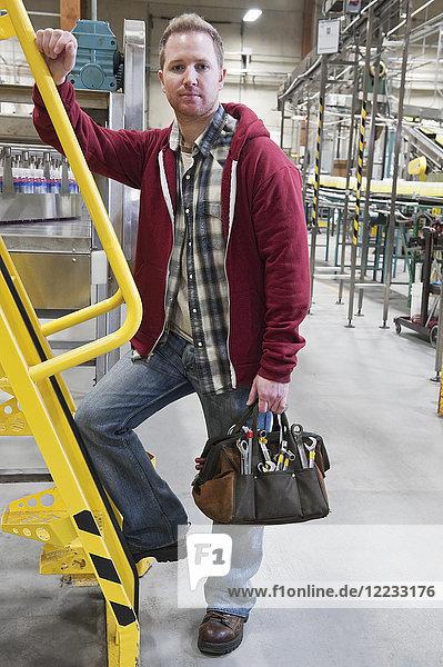 Porträt eines Mannes  der mit seiner Werkzeugtasche zur Arbeit in einer Lagerabfüllanlage eintrifft.