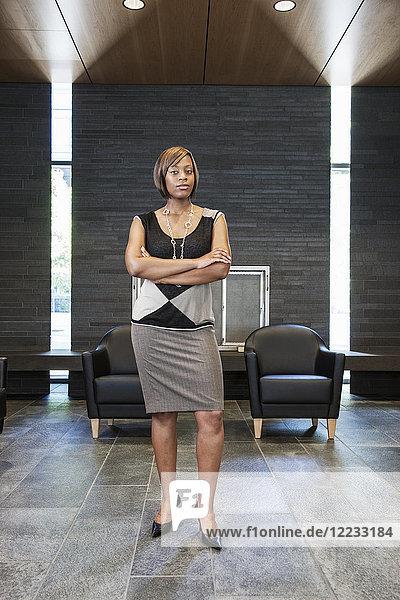 Schwarze Geschäftsfrau in der Lobby eines großen Bürogebäudes.