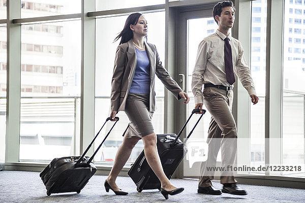 Geschäftsleute  die auf dem Weg zum Flugzeug durch einen überdachten Gang gehen.