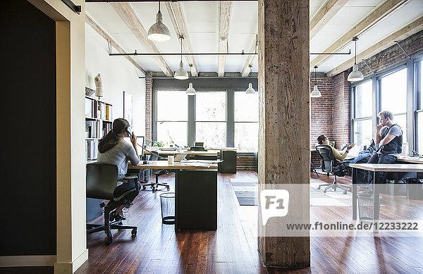 Asiatische Frau  die an ihrem Schreibtisch in einem kreativen Büro arbeitet.