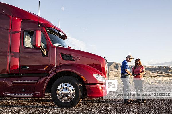 Das Fahrerteam aus Ehemann und Ehefrau prüft ihre Reiseroute  während sie vor ihrem Lastwagen stehen.