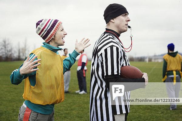 Kaukasisches weibliches Mannschaftsmitglied streitet mit einem Schiedsrichter  während es berührungslosen Flaggenfußball spielt.
