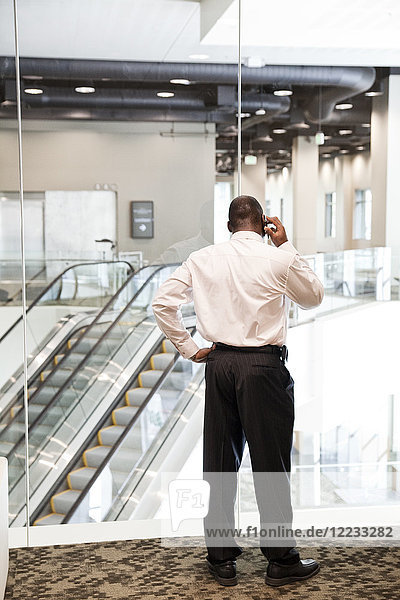 Schwarzer Geschäftsmann am Telefon in der Lobby eines großen Geschäftszentrums.