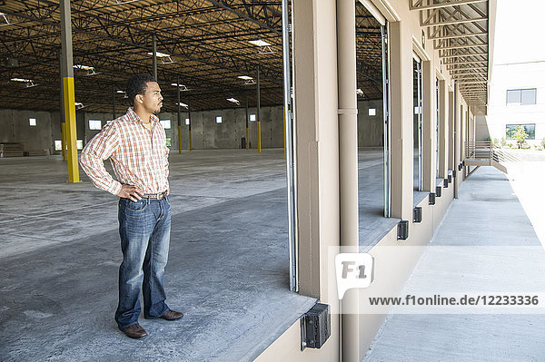 Black man standing in loading dock door of new empty warehouse anticipating the arrival of the first truck load new business.