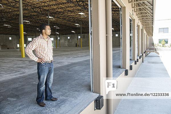 Schwarzer Mann steht in der Tür der Laderampe eines neuen leeren Lagers und erwartet die Ankunft der ersten Lkw-Ladung neuer Geschäfte.