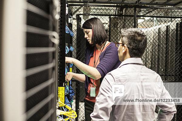 Kaukasische Technikerinnen und Techniker  die in einer großen Computer-Serverfarm an CAT 5-Kabeln arbeiten.