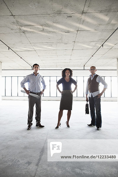 Mixed race team of business people in their new large empty raw office space.