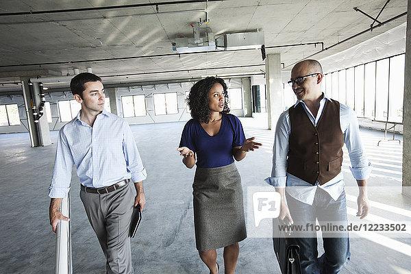 Gemischtes Rennteam von Geschäftsleuten  die einen neuen  leeren  rohen Büroraum besichtigen.