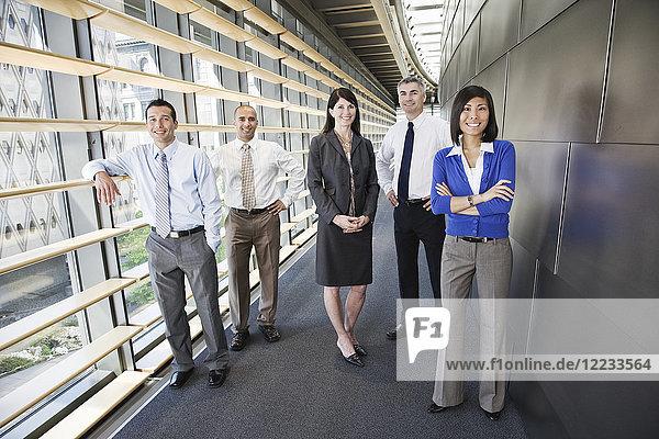 Gemischtrassiges Team von Geschäftsleuten in der Lobby eines großen Bürogebäudes.