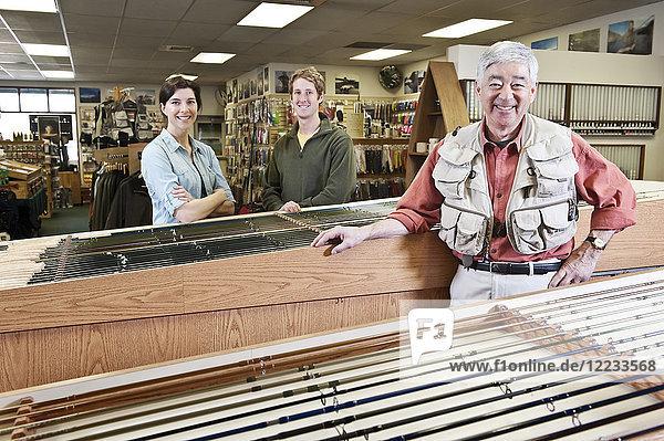 Asiatisch-amerikanischer älterer männlicher Besitzer eines Einzelhandelsgeschäfts für Fliegenfischerei und kaukasische männliche und weibliche Angestellte im Hintergrund. Der Ladenbesitzer trägt eine Fliegenfischerweste.