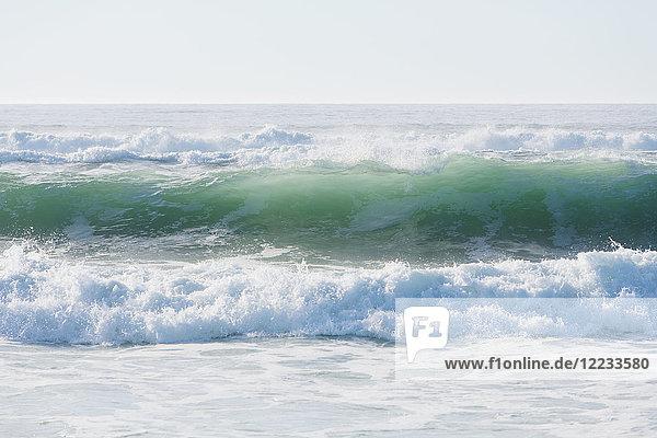 Meereslandschaft mit brechenden Wellen am Sandstrand.