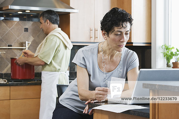 A man cooking supper at the hob  and a woman using a laptop and checking paperwork in the kitchen.