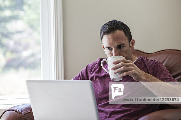 Caucasian business man using a lap to for work at home in a chair.