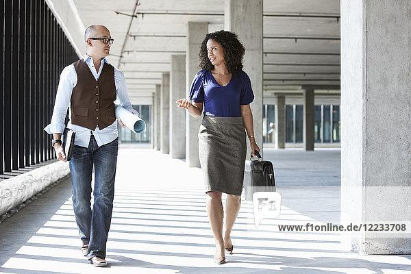 Ein asiatischer Geschäftsmann und eine schwarze Geschäftsfrau gehen durch einen großen leeren Büroraum  der von der Nachmittagssonne beleuchtet wird.