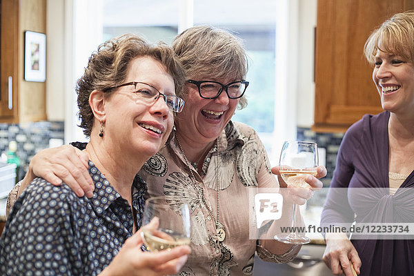 A group of senior women friends having some wine at a home dinner party.