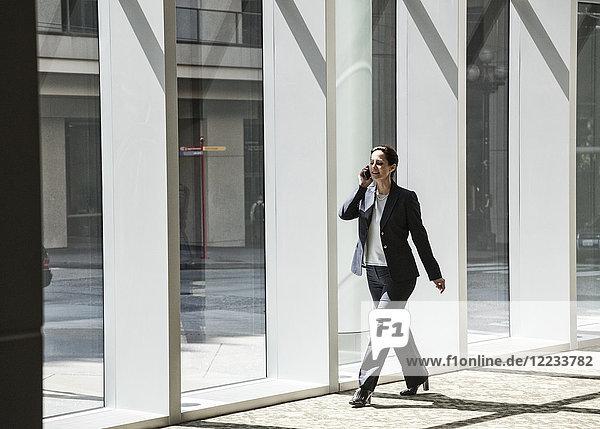 Geschäftsfrau am Telefon und beim Gang durch die Lobby eines großen Geschäftszentrums.
