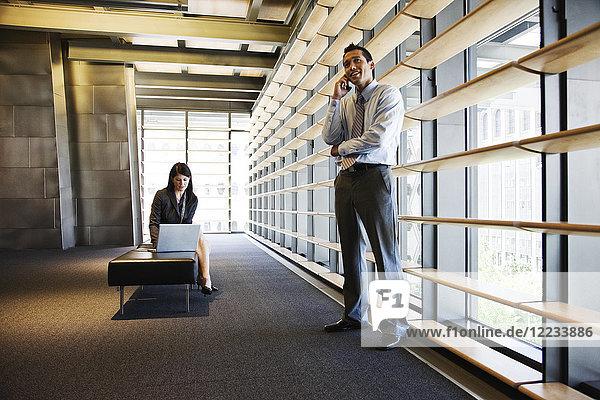 Geschäftsfrau und Geschäftsmann  die in der Lobby eines großen Bürogebäudes arbeiten.