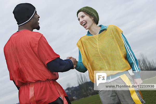 Schwarzer Mann und kaukasische weibliche Teammitglieder schütteln sich bei einer Sportveranstaltung die Hand.