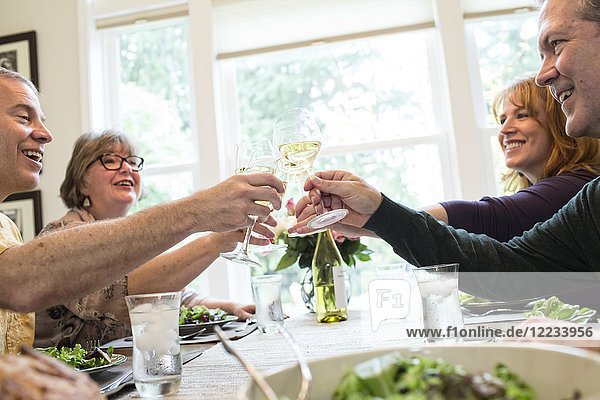 Senior couples toasting a home dinner party with glasses of white wine.