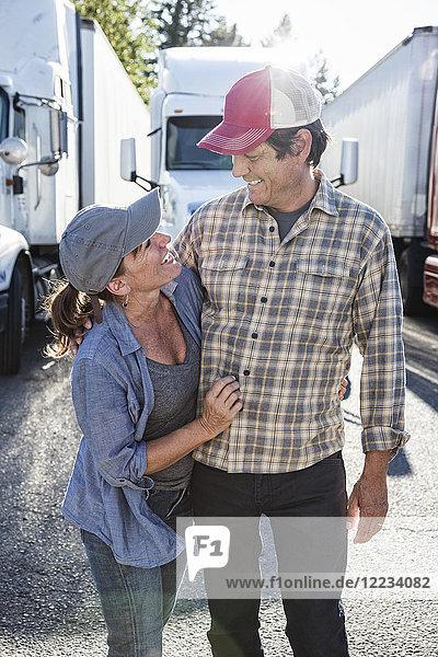 Ein Lastwagenfahrerteam aus Ehemann und Ehefrau in der Nähe ihres Lastwagens parkte auf einem Parkplatz an einer Raststätte.