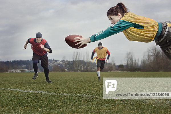 Caucasian woman diving with a football during a non-contact flag football match.