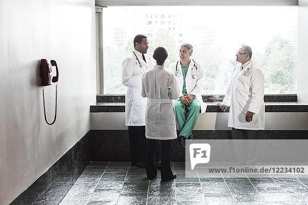 Ärzte gemischter Rasse beraten sich in einem Krankenhausflur.