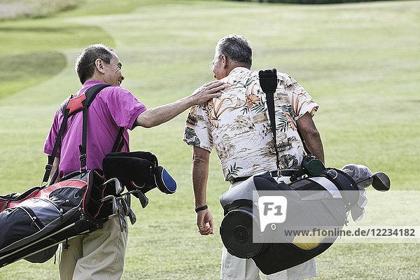 Two senior friends golfing and walking on a fairway toward their next shots.