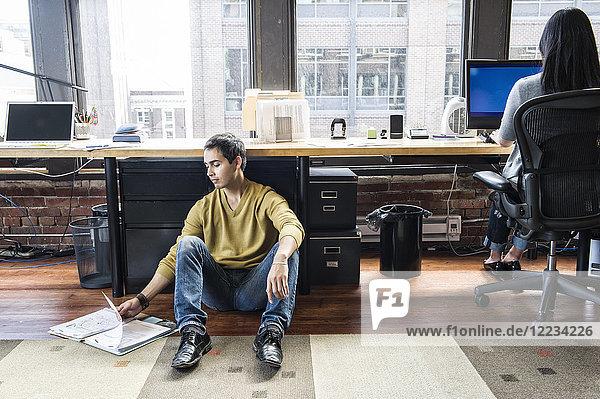 Lateinamerikanischer Mann  der auf einem Bodennetz zu seinem Arbeitsplatz in einem kreativen Büro sitzt.