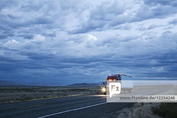 Kommerzieller Lastwagen bei Sonnenuntergang auf der Straße.
