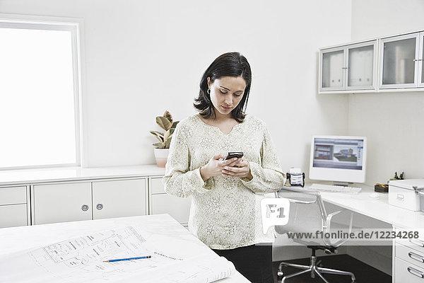 Hispanische Frau  die in einem Architekturbüro am Handy arbeitet