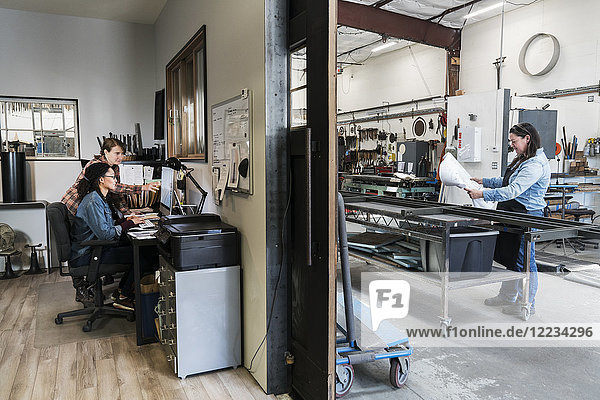 Two women at a desk in office area of a metal workshop  woman standing at mobile workbench.
