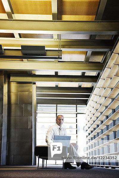 Geschäftsmann  der in der Lobby eines großen Bürogebäudes an einem Laptop-Computer arbeitet.