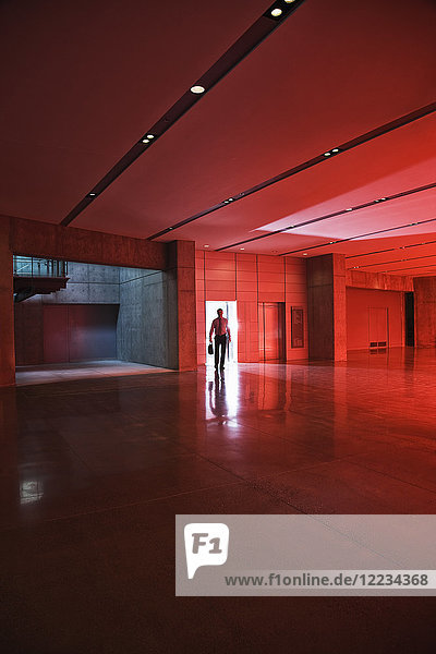 Businessman walks through the door of a lobby area that is lit by daylight through red tinted glass.