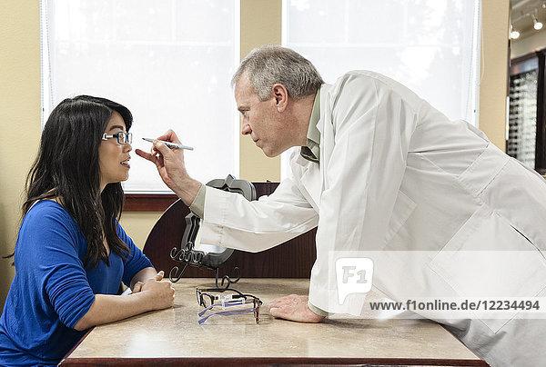 Kaukasischer Augenarzt  der mit einer Asiatin zusammenarbeitet  die sich eine neue Brille kauft.