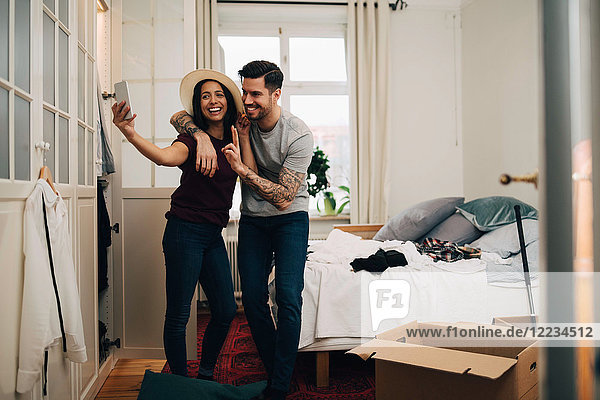 Smiling couple taking selfie on mobile phone while standing in bedroom