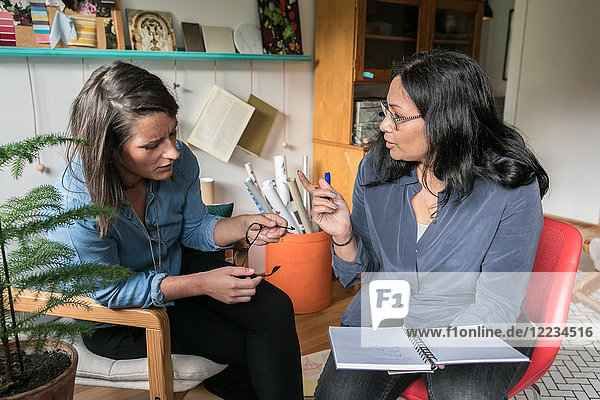 Female colleagues discussing over book while sitting in home office