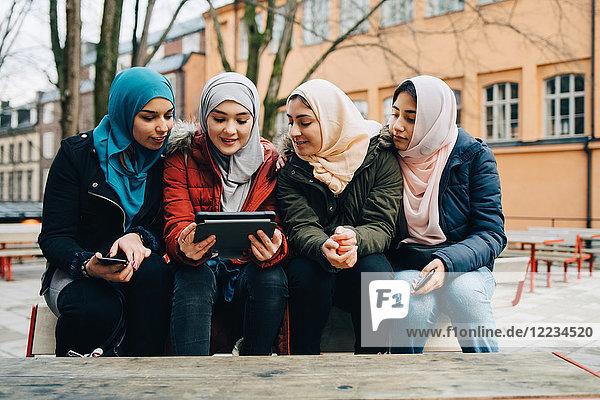 Female Muslim friends sitting on bench sharing digital tablet in city