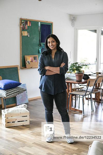 Porträt einer Geschäftsfrau mit gekreuzten Armen im Home-Office stehend