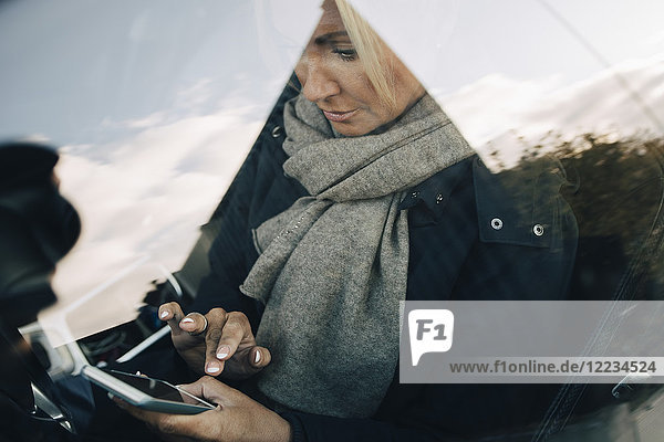 High angle view of mature woman using mobile phone sitting car