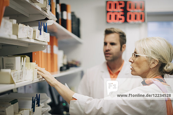 Mature medical colleagues arranging medicines on rack at pharmacy store