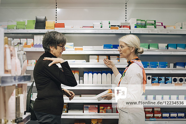 Side view of senior female customer explaining to owner standing by medicine rack at pharmacy store