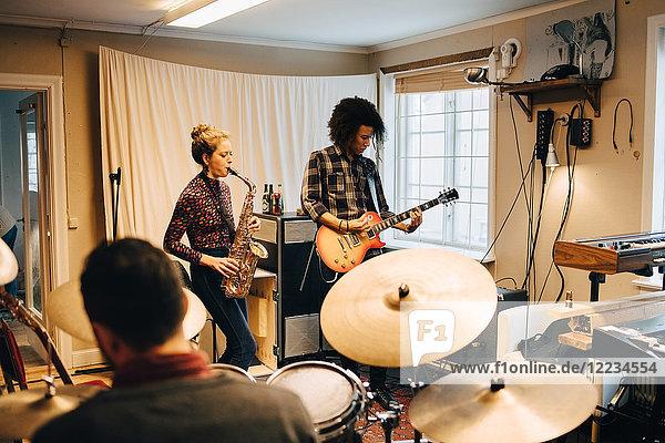 Freunde beim Spielen von Musikinstrumenten im Studio