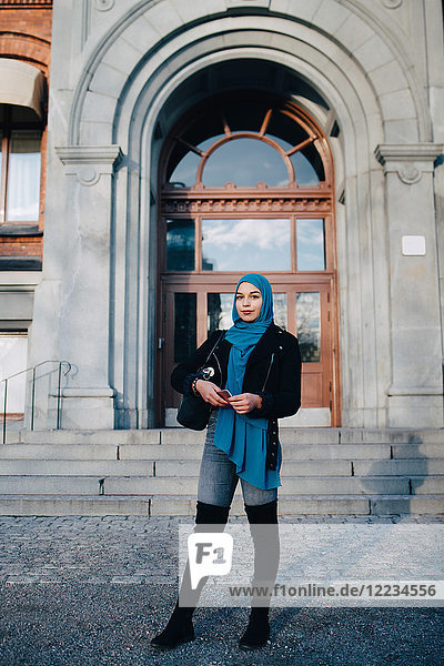 Full length portrait of confident young Muslim woman standing with smart phone against entrance door
