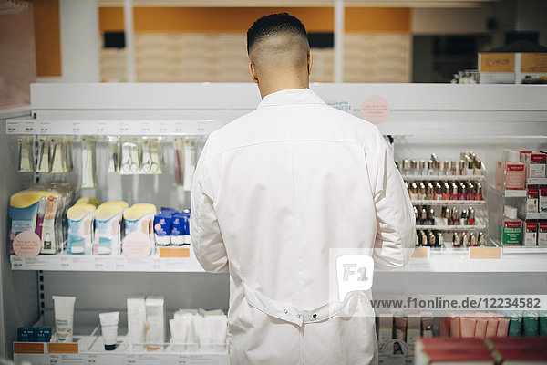Rear view of male owner arranging medicines on rack at pharmacy store