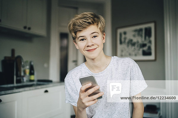 Portrait of smiling teenage boy holding smart phone while sitting in kitchen at home