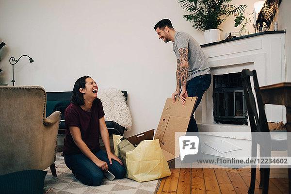 Fröhliches Paar beim Auspacken von Kisten im Wohnzimmer im neuen Zuhause