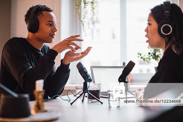 Männlicher Blogger gestikuliert zu einer Frau  die Kopfhörer am Tisch trägt