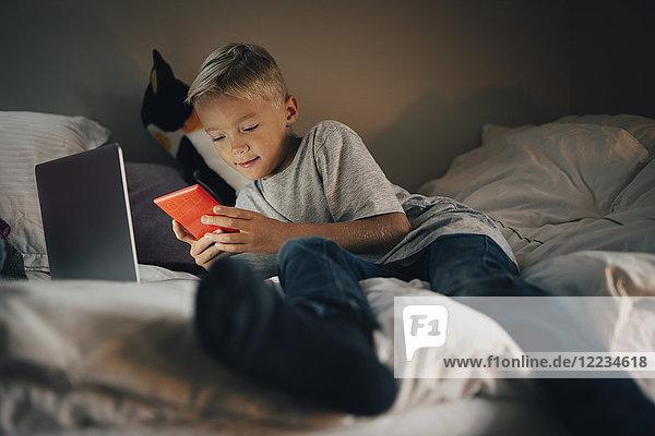 Volle Länge des Jungen mit dem Handy liegend mit Laptop auf dem Bett zu Hause
