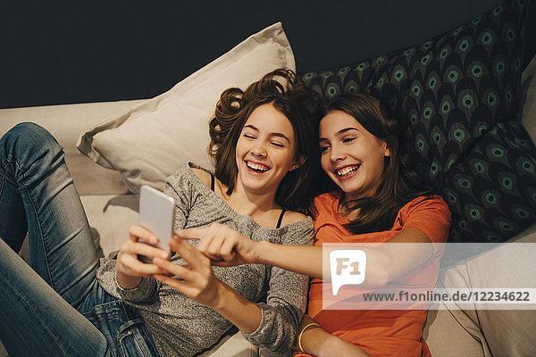 Hochwinkelansicht von glücklichen Freunden  die das Telefon benutzen  während sie sich zu Hause auf dem Sofa ausruhen.